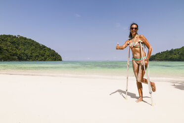 Thailand, Koh Surin island, woman with crutches standing at the white sandy beach - MBEF000726