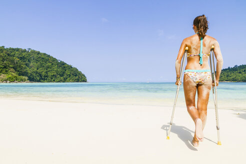 Thailand, Koh Surin island, woman with crutches walking at the white sandy beach - MBEF000729