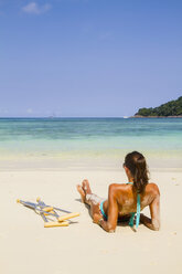 Thailand, Koh Surin island, woman with crutches lying at the white sandy beach - MBEF000725