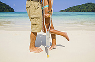 Thailand, Koh Surin island, woman with crutches kissing man at the white sandy beach - MBEF000728