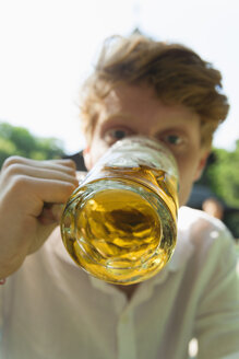 Young man drinking beer outdoors - TC003561