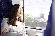 Germany, Brandenburg, Mid adult woman looking through window in train - KFF000219