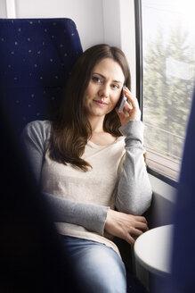 Germany, Brandenburg, Portrait of mid adult woman talking on smart phone in train - KFF000220