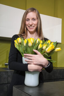 Smiling woman with bunch of tulips in kitchen - RDF001168