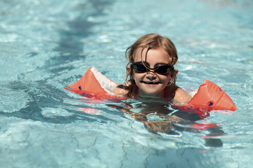 Germany, Bavaria, Girl swimming with goggles, smiling - STB000038