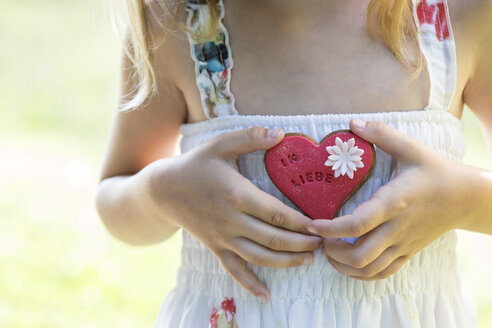 Germany, Bavaria, Girl holding heart shaped biscuit, close up - STB000046