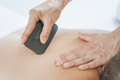 Traditional Chinese Medicine, TCM, female therapist during Gua Sha therapy - MJF000376