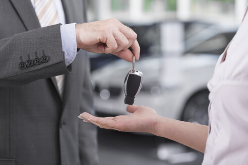 At the car dealer, Salesman handing over car key to client - MLF000034