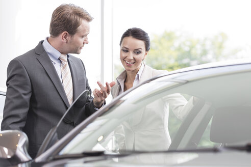 At the car dealer, Salesman showing new car to client - MLF000017
