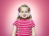 Smiling young girl listening to headphones - STKF000347