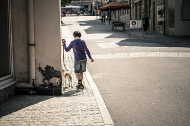 Germany, Vaihingen, Little boy walking dog - SBDF000206