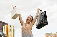 Germany, Berlin, Potsdam Square, happy young woman with two shopping bags - BFR000247