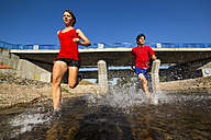 Germany, Baden-Wuerttemberg, Winterbach, athletic young man and young woman running through Rems river - STSF000114