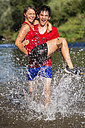 Germany, Baden-Wuerttemberg, Winterbach, athletic young man carring young woman while running through Rems river - STSF000124
