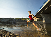 Germany, Baden-Wuerttemberg, Winterbach, athletic young woman running through Rems river - STSF000117