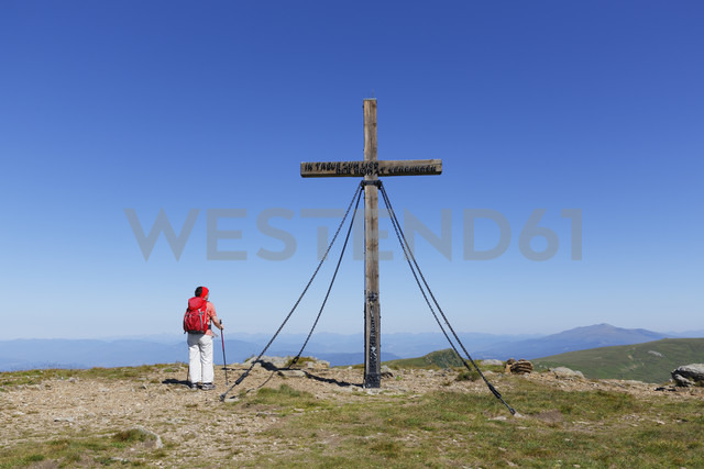 Austria, Carinthia, Saualpe, Ladinger Spitz, woman standing nearby the summit cross - SIE004360