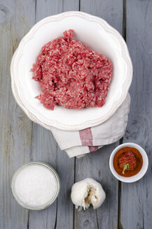 Raw ground beef, sea salt, garlic and paprika on wooden table - ODF000435