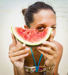 Thailand, Koh Surin island, woman holding a slice of watermelon in her hands at the beach, close-up - MBEF000732