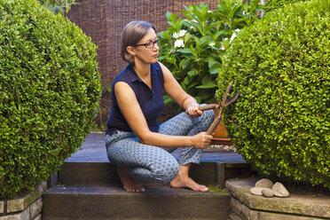 Germany, Stuttgart, Woman cutting box tree - WDF001956