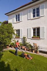 Germany, Stuttgart, Woman mowing lawn - WDF001929