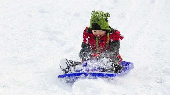 Germany, Bavaria, smiling little boy sledging down a hill - RDF001166