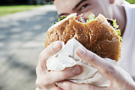 Young man showing his hamburger - FEXF000036