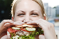 Young woman eating a hamburger - FEXF000039