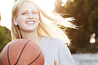 Smiling young woman with basketball - FEXF000049