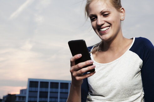 Smiling young woman with smart phone - FEXF000019