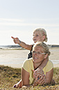 France, Bretagne, Landeda, Mother and daughter lying at the coast - LAF000123