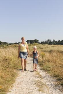 France, Bretagne, Landeda, Mother and daughter walking on dune path - LAF000126