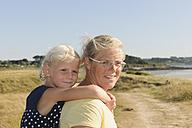 France, Bretagne, Landeda, Mother carrying daughter piggyback - LAF000129