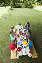 Children sitting at table on a birthday party - NHF001423