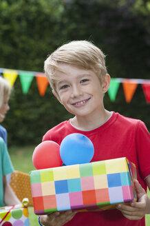 Boy holding birthday present - NHF001438