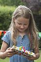 Girl holding birthday present - NHF001432