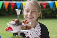Girl looking at muffins on a birthday party - NHF001470