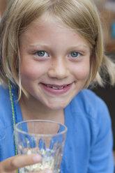 Smiling girl holding glass, portrait - NHF001444