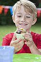 Happy boy eating muffin on a birthday party - NHF001446