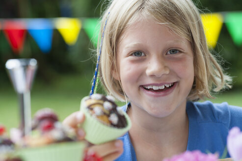 Happy girl eating muffin on a birthday party - NHF001434