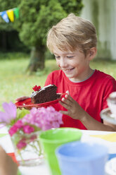 Happy boy holding plate with cake on a birthday party - NHF001452