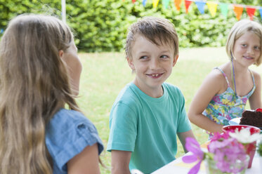 Children sitting at table on a birthday party - NHF001453