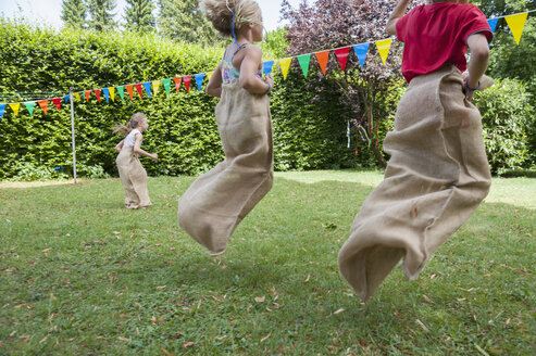 Children having a sack race in garden on a birthday party - NHF001461