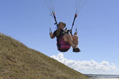 France, Bretagne, Landeda, Man paragliding - LAF000157
