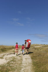 France, Bretagne, Landeda, Father with two sons walking in dune - LAF000159