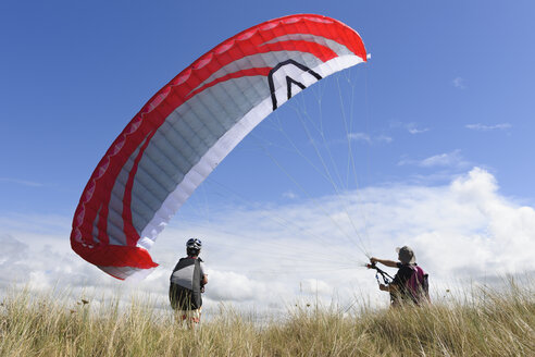 France, Bretagne, Landeda, Father and son with paraglider in dune - LAF000170