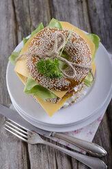 Two sesame bagels with Gouda and lettuce leaf, studio shot - ODF000471