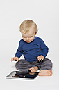 Happy baby boy playing with tablet PC, studio shot - MUF001407