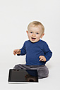 Happy baby boy playing with tablet PC, studio shot - MUF001406