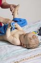 Mother drying baby boy after bath, studio shot - MUF001396