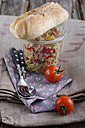 Couscous salad in glass jar with baguette bread and tomatoes, close up - ODF000476